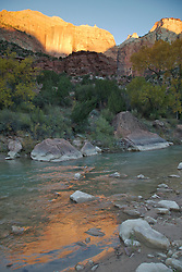 A mountain reflects in the Virgin River at sunrise in Zion National Park, Utah.