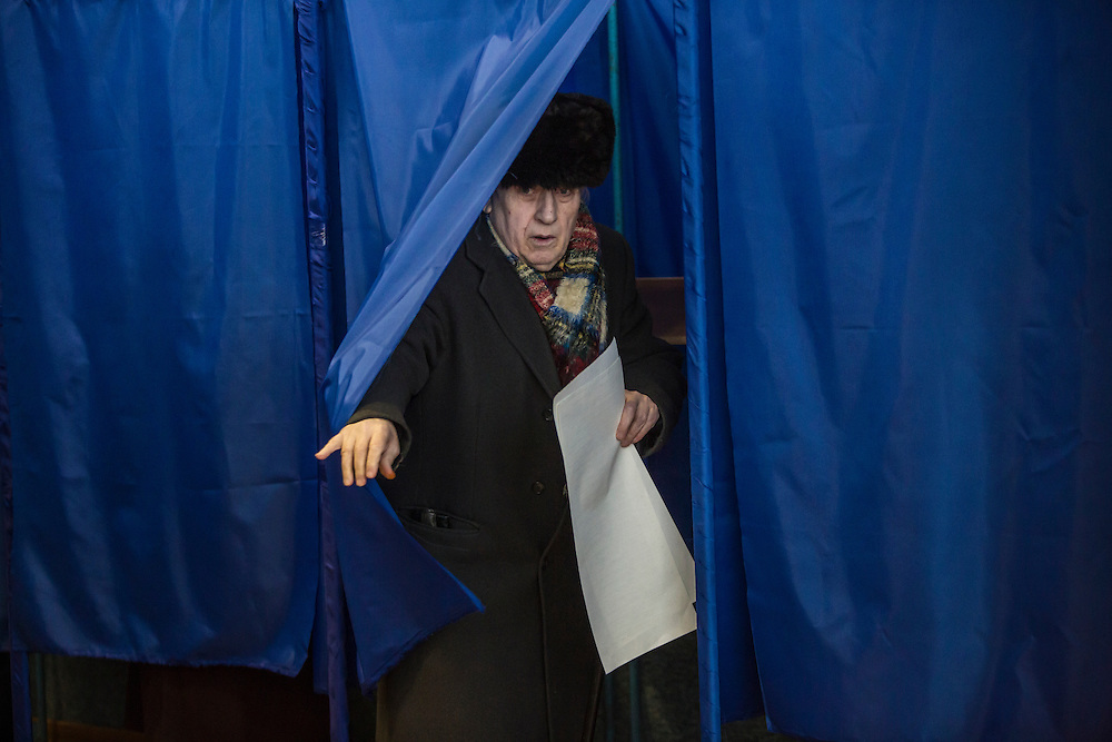 KIEV, UKRAINE - OCTOBER 26: A man emerges from a voting booth with his ballot for parliamentary elections after casting his vote at a polling station on October 26, 2014 in Kiev, Ukraine. The country's parliamentary elections are seen as key to President Petro Poroshenko's ability to advance his agenda. (Photo by Brendan Hoffman/Getty Images) *** Local Caption ***
