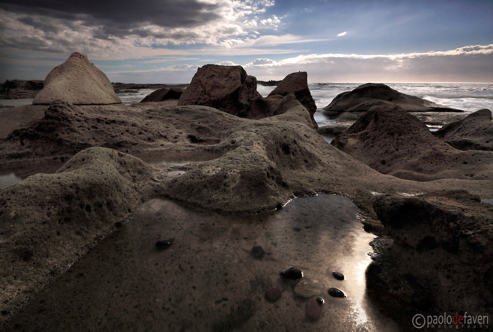 The amazing wind carved rocky sculptures at the beach of Torre Argentina, not far from the small, pictoresque town of Bosa in Sardinia, Italy. Taken on a calm and serene night of mid September, stitched from five vertical frames.