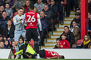 Julian Jeanvier (Brentford) on the ground following a tackle with Tom Lawrence (Derby County) and Ezri Konsa Ngoyo (Brentford) came over and took hold of Tom Lawrence (Derby County) shirt during the EFL Sky Bet Championship match between Brentford and Derby County at Griffin Park, London, England on 6 April 2019.