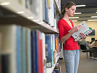 Teenage student reading text books by library shelf