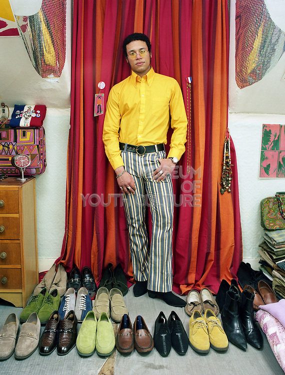 Young man standing in front of colourful curtain with several pairs of shoes on the floor around him.