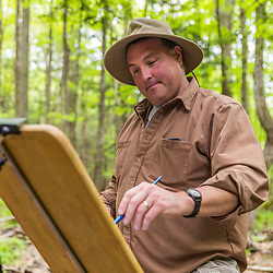 A man paints in the woods at the Orris Falls Preserve in South Berwick, Maine.