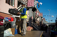 MANENBERG, SOUTH AFRICA - SEPTEMBER 11: Residents and construction workers load the belongings of residents in a government housing area as the units are refurbished and upgraded on September 11, 2013 in Manenberg, a township of Cape Town, South Africa. A dispute with the city and local community organizations over plans for construction has slowed the process. Photo by Ann Hermes/The Christian Science Monitor