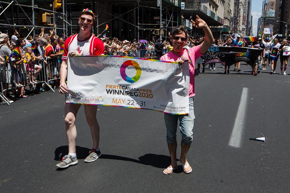 New York, NY - 30 June 2019. The New York City Heritage of Pride March filled Fifth Avenue for hours with participants from the LGBTQ community and it's supporters. Two marchers from Winnipeg carry a banner announcing 2020 Canada Pride.