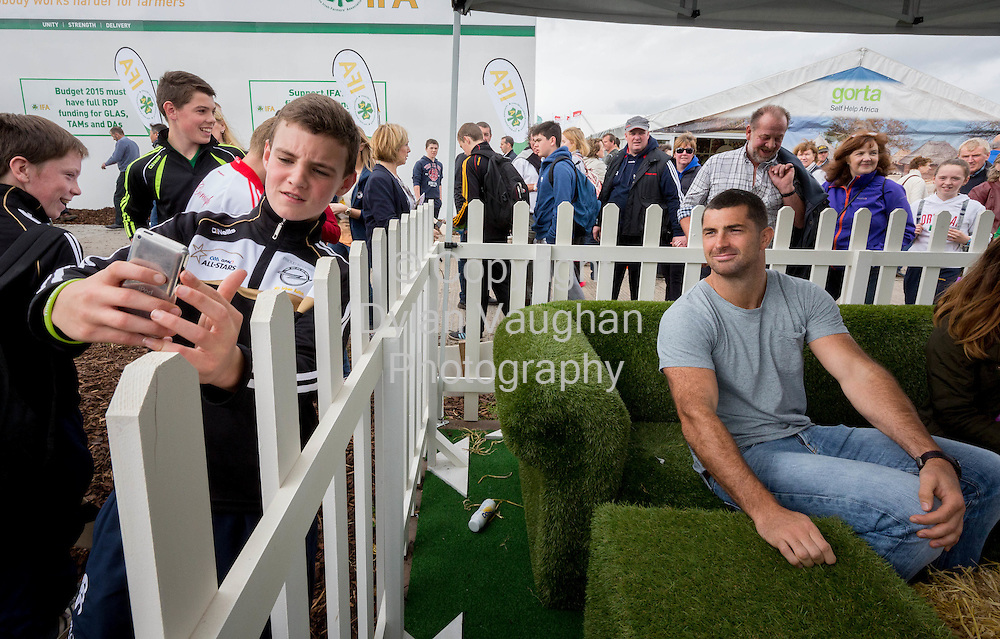 Repro Free no charge for Repro<br /> <br /> 23-9-14<br /> Rob and Dave Kearney to Join NDC at Ploughing &amp; Judge &lsquo;Welly Line Out&rsquo; NDCDome at ploughing: Block 3/ Row 21/ Stand 306<br />  <br /> Rugby professionals Rob and Dave Kearney joined the National Dairy Council on the first day of the National Ploughing Championships at Ratheniska, Co. Laois (Tuesday 23rd September, 2014) where they took part in on-stage discussions in the NDC Dome, met members of the public and judged a colourful &lsquo;Welly Line Out&rsquo;.<br />  <br /> Rob and Dave Kearney are ambassadors to the NDC, helping to highlight the importance of starting good habits young in relation to diet and exercise; showcasing the natural goodness of Ireland&rsquo;s pasture based dairy farming and promoting the positive role that milk may play in a number of aspects of sports nutrition, based on emerging scientific research in this area.    They feature in an NDC advertisement campaign (It All Starts Here) filmed on the farm in the Cooley Peninsula where Rob and Dave grew up.<br />  <br /> Pictured is Liam Gorman aged 13 from Mullingar taking a selfie with Rob Kearney.<br /> Picture Dylan Vaughan