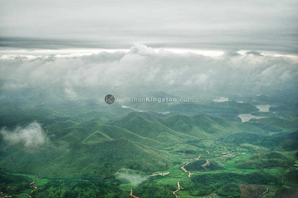 Aerial view of mountains, clouds, a river and terraced farmland near Guilin, China.