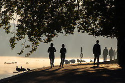 © Licensed to London News Pictures. 27/09/2018. London, UK. Joggers in Hyde Park at sunrise this morning. The temperature in the capital is set to reach 22 degrees Celsius later today. Photo credit : Tom Nicholson/LNP