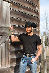 hot masculine cowboy by a rustic barn