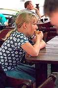 Girl age 11 eating ice cream cone in sidewalk cafe.  Warsaw Poland