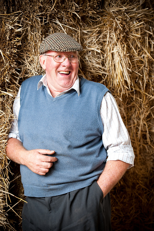 Laughing older senior farmer in rolled up sleeves and a cap standing in front of fresh hay bales