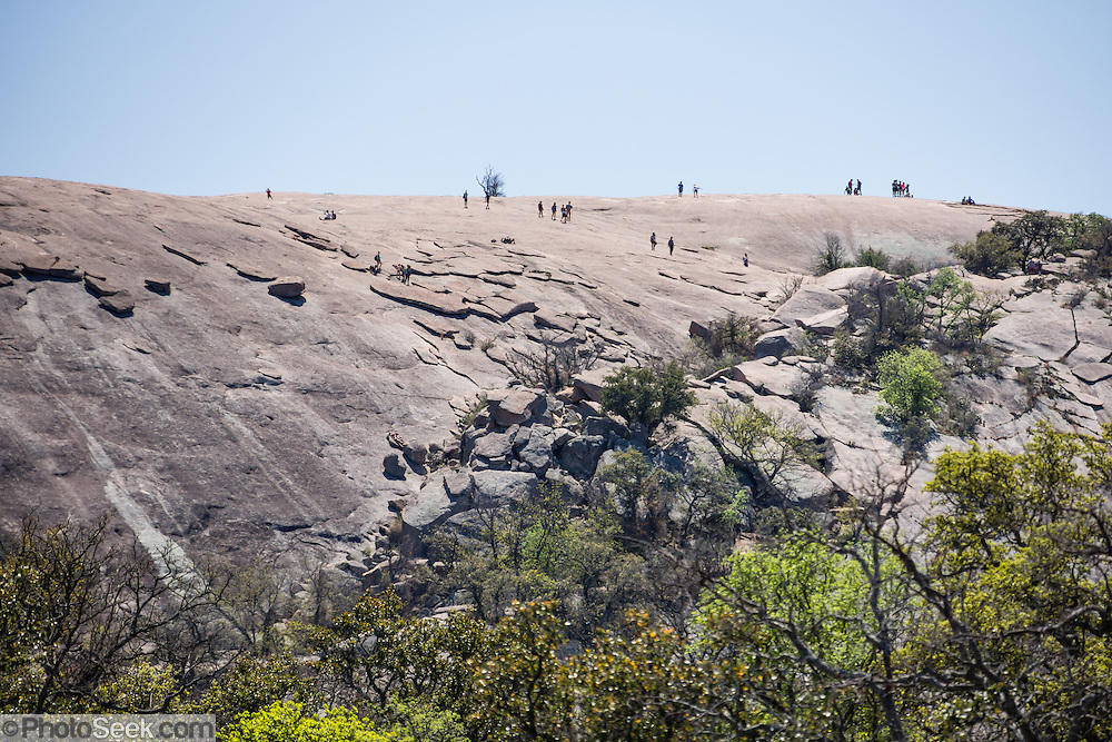 "Hikers explore atop Enchanted Rock. Explore a large pink granite dome at Enchanted Rock State Natural Area, between Fredericksburg and Llano, Texas, USA. Enchanted Rock is a fascinating exfoliation dome (with layers like an onion), rising 425 feet (130 m) above its surroundings to elevation of 1825 feet (556 m) above sea level, in the Llano Uplift. Geologically, the exposed rock (monadnock or inselberg, ""island mountain"") is part of a pluton (bubble of rock slowly crystallized from magma) within the billion-year-old igneous batholith, Town Mountain Granite (covering 62 square miles mostly underground), which intruded from a deep pool of hot magma 7 miles upwards into the older metamorphic Packsaddle Schist. The overlying sedimentary rock (Cretaceous Edwards limestone) eroded away to expose the prominent domes seen today: Enchanted Rock, Little Rock, Turkey Peak, Freshman Mountain, and Buzzard's Roost."