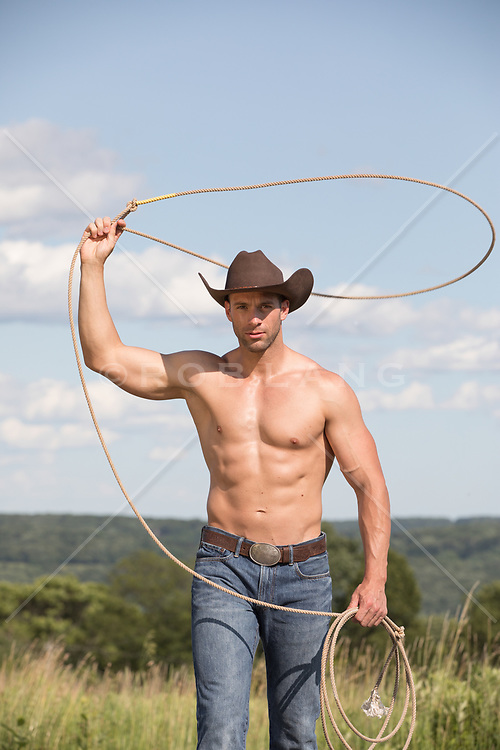 shirtless muscular cowboy with a lasso on a ranch