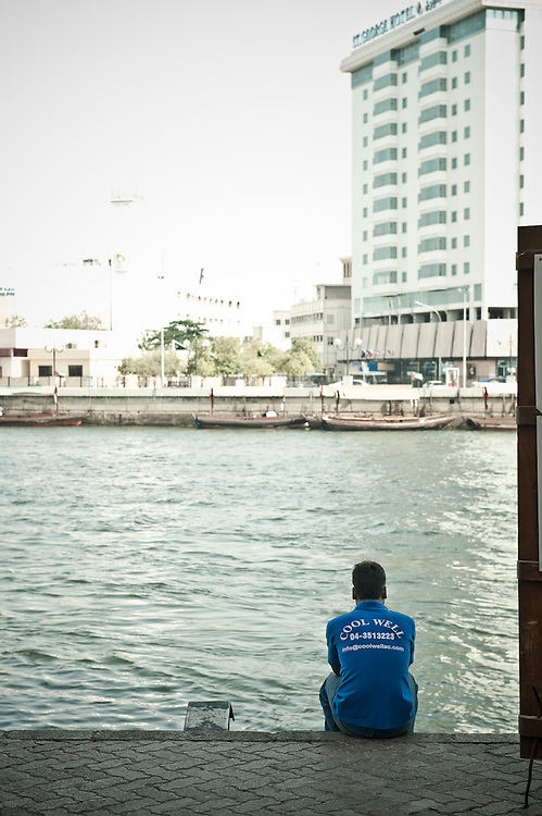 A man sits by the Dubai creek Archive of images of Dubai by Dubai photographer Siddharth Siva