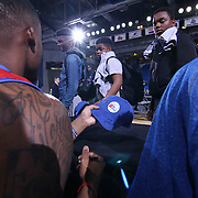 Delaware 87ers Guard Maalik Wayns (12), LEFT, signs a hat for a young fan after a NBA D-league regular season basketball game between the Delaware 87ers and the Grand Rapids Drive (Detroit Pistons) Saturday, Apr. 04, 2015 at The Bob Carpenter Sports Convocation Center in Newark, DEL.