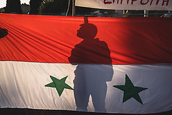 April 13, 2018 - Athens, Greece - A protester's silhouette seen behind the flag of Syria...Anti-war concentration by various social communities. With slogans such as ''The navy should leave the Aegean and the Mediterranean sea'' and ''Yes to Friendship and Solidarity of People'' after a march, hundreds of protesters arrived outside the US Embassy in Athens. (Credit Image: © Vangelis Evangeliou/SOPA Images via ZUMA Wire)
