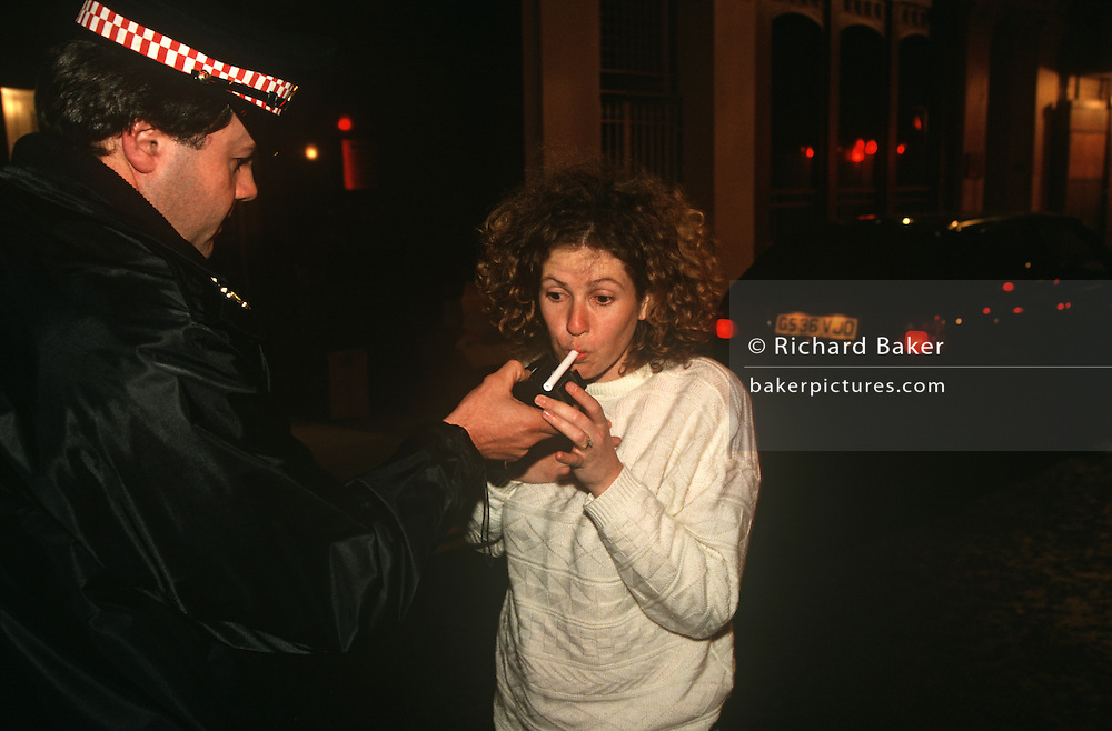 A woman driver is breathalysed by an officer from the City of London Police. .The first practical roadside breath-testing device intended for use by the police was the drunkometer. The drunkometer was developed by Professor Harger in 1938. The drunkometer collected a motorist's breath sample directly into a balloon inside the machine. The breath sample was then pumped through an acidified potassium permanganate solution. If there was alcohol in the breath sample, the solution changed colour. The greater the colour change, the more alcohol there was present in the breath.