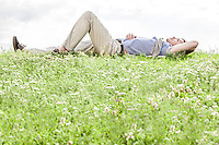 Full length of young man lying on grass against sky