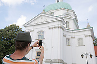 Rear view of young man photographing St. Casimir Church; Warsaw; Poland