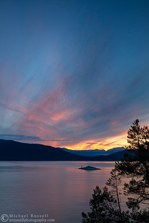 Sunset over Howe Sound from Juniper Point at Lighthouse Park in West Vancouver, British Columbia, Canada. In the background you can see the Grebe Islets, Bowen Island, and the mountain peaks in the Sunshine Coast's Tetrahedron Range.