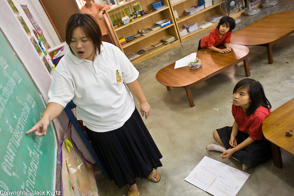 """19 FEBRUARY 2008 -- SANGKLABURI, KANCHANABURI, THAILAND: A Karen woman teaches Burmese children the Thai language at the Baan Unrak School in Sangklaburi, Thailand. The school's curriculum is in Thai, but many of the Burmese children don't speak Thai, so they have to take remedial Thai. Baan Unrak children's home and school, established in 1991 in Sangklaburi, Thailand, gives destitute children and mothers a home and career training for a better future. Baan Unrak, the """"Home of Joy,"""" provides basic needs to well over 100 children, and  abandoned mothers. The home is funded by donations and the proceeds from the weaving and sewing shops at the home. The home is a few kilometers from the Burmese border. All of the women and children at the home are refugees from political violence and extreme poverty in Burma, most are Karen hill tribe people, the others are Mon hill tribe people. The home was started in 1991 when Didi Devamala went to Sangklaburi to start an agricultural project. An abandoned wife asked Devmala to help her take care of her child. Devmala took the child in and soon other Burmese women approached her looking for help.    Photo by Jack Kurtz"""