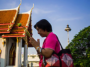 04 MARCH 2015 - BANGKOK, THAILAND:  A woman carries a lotus bud and incense while she prays and walks around the prayer hall at Wat Benchamabophit on Makha Bucha Day. Makha Bucha Day is an important Buddhist holy day and public holiday in Thailand, Cambodia, Laos, and Myanmar. Many people go to temples to perform merit-making activities on Makha Bucha Day. Wat Benchamabophit is one of the most popular Buddhist temples in Bangkok.   PHOTO BY JACK KURTZ