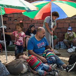 A refugee family waits at the reception center in Macedonia on August 26, 2015. After crossing from Greece into Macedonia, refugees are held at a reception center near the town of Gevgelija. To transit through Macedonia they receive a document allowing them 72 hours to apply for asylum or leave the country. Most continue north to other European states.