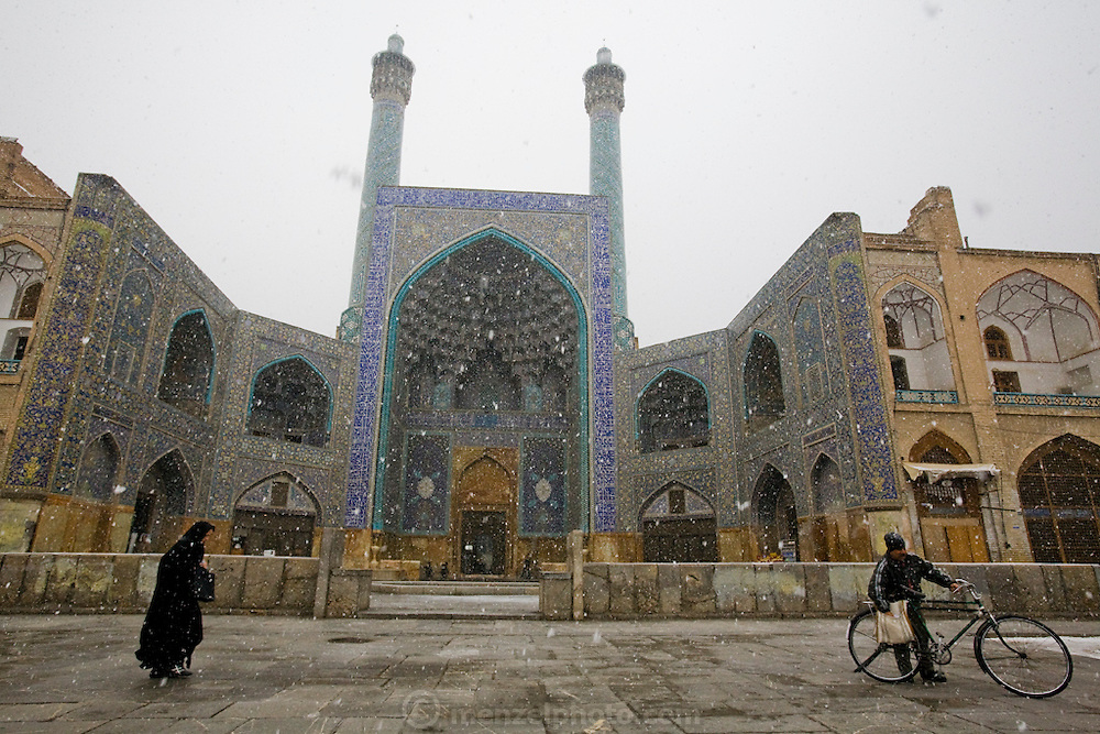 People walk across the forecourt of the Sheikh Lotfollah Mosque in the city of Isfahan, Iran. The  extravagantly tiled and decorated private mosque is in Imam Square, also known as Naghsh-i Jahan Square in Isfahan.