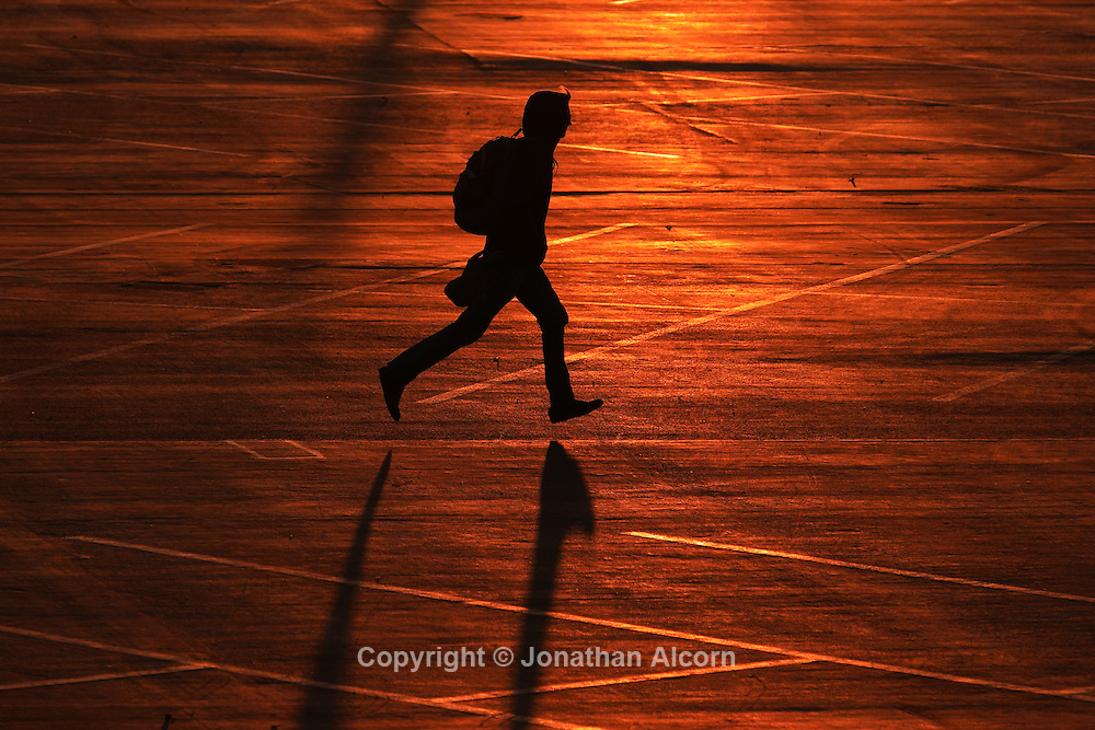 A man wearing a backpack runs across an empty parking lot that reflects the orange glow of sunset