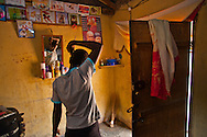 Young woman in the village of Aliade, Nigera, checks her appearance before venturing outside.