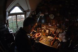 Horologist and time piece repairer & restorer in his workshop UK