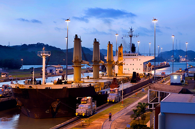 A ship is lowered into the Miaraflores Locks, one of three locks on the Panama Canal that allow ships to transit through the canal.  Locomotives help maneuver the ship through the lock and back into the canal.