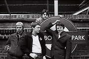Four friends with Westbourne park tube station sign in 1980s. London, Westbourne, UK, 1980s.