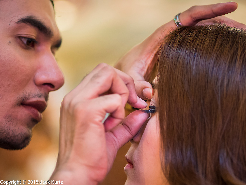 25 MARCH 2015 - BANGKOK, THAILAND: A contestant gets her eyelashes put on during the first round of the Miss Tiffany's contest at CentralWorld, a large shopping mall in Bangkok. Miss Tiffany's Universe is a beauty contest for transgender contestants; all of the contestants were born biologically male. The final round will be held on May 8 in the beach resort of Pattaya. The final round is televised of the  Miss Tiffany's Universe contest is broadcast live on Thai television with an average of 15 million viewers.     PHOTO BY JACK KURTZ