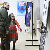 Caroline Carlisle, 10 and her Uncle Justin Smith view the paintings of the artists at the Link Centre's reception Saturday