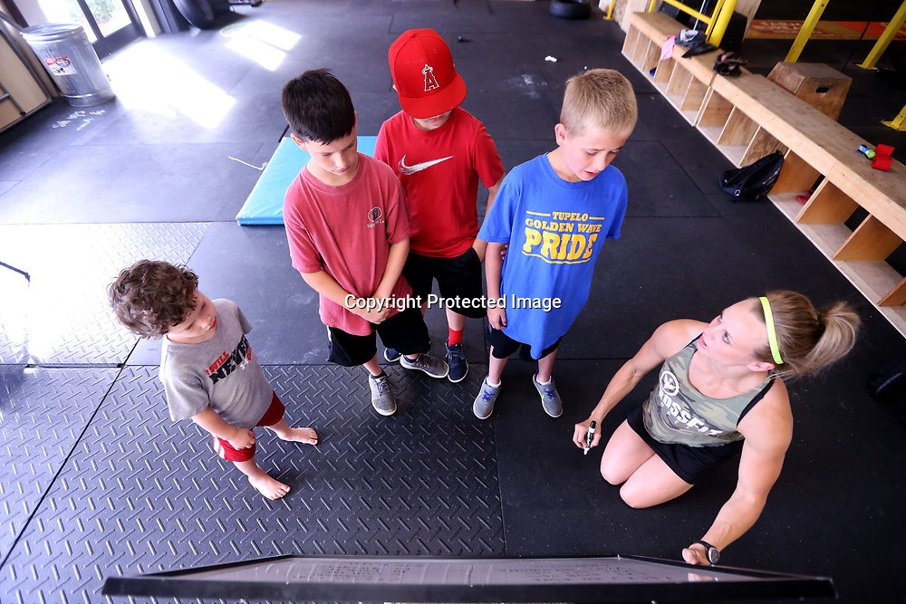 "Tiffany Anderson, right, the Kids Program Instructor at CrossFit in Tupelo, goes over the ""Little Murph"" work out with Tripp Blankenship, 4, his two brothers, Turner, 10, Tatum, 9, and Anderson's son, Emil, 10, on Memorial Day morning at the CrossFit gym in Tupelo. The children took part in the Memorial Day Murph Challenge which they called the ""Little Murph"", that includes 50 pull-ups, 100 sit-ups, 200 air squats and a 400 meter run. The Murph is a workout in the honor of fallen Navy Lieutenant Michael Murphy."