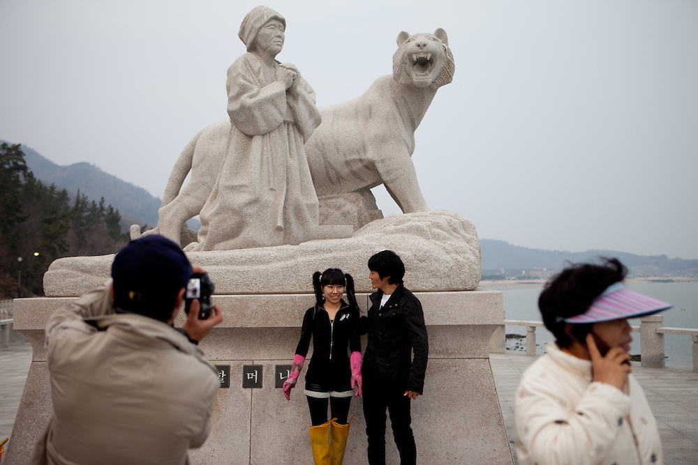 "Visitors getting photographed at the monument in Hoedong (Jindo island) which is showing praying grandmother ""Old Lady Pong"" and a tiger related to the Jindo myth. Jindo is the 3rd biggest island in South Korea located in the South-West end of the country and famous for the ""Mysterious Sea Route"" or ""Moses Miracle"" which is happening during full moon in spring."