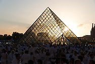"""France. Paris Musee du Louvre main courtyard. The Dîner en Blanc, or impromptu """"dinner in white,"""" in  the Louvre in Paris. Participants, all dressed up in white, arrive for the 25th Diner en Blanc in Paris. The locations of the annual """"dinner in white"""" are kept secret from the Paris authorities, and the invited participants are only told where they are to gather earlier in the evening."""