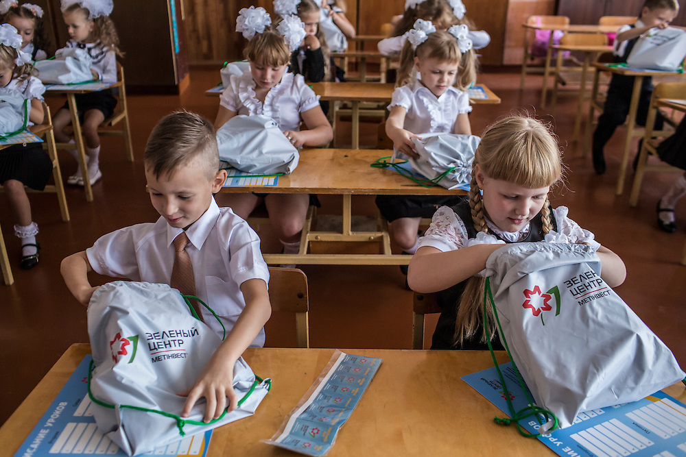 MARIUPOL, UKRAINE - SEPTEMBER 1, 2015: Students in the first class at School 68 open bags with school supplies donated by Metinvest, a mining and steel conglomerate based in eastern Ukraine, on the first day of the new school year in Mariupol, Ukraine. On January 24 of this year, shelling in the same neighborhood killed 31 people, all civilians, and while much recent fighting has been concentrated near Mariupol, a drop in ceasefire violations in the past few days has been credited to a desire to not interfere with the start of the new school year. CREDIT: Brendan Hoffman for The New York Times