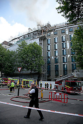© Licensed to London News Pictures. LONDON, UK  14/06/11. Smoke pours from the roof of a building on fire on Aldwich in London today (Tuesday). Please see special instructions for usage rates. Photo credit should read Matt Cetti-Roberts/LNP