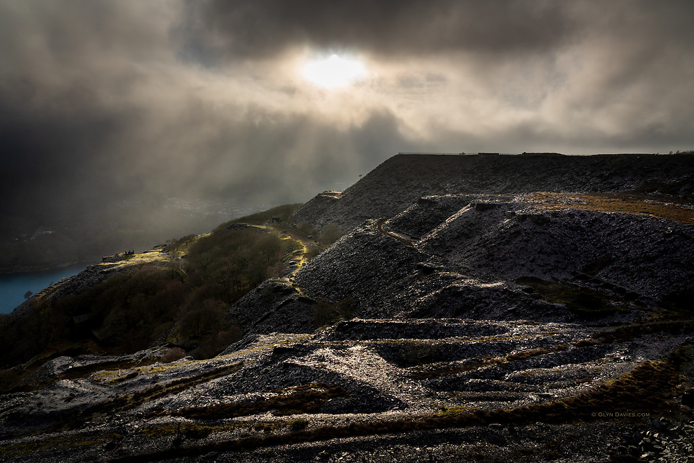 The massif of Snowdon tries to hold back an enormous fog bank from the Irish Sea, but clouds and fog spilled over nevertheless. Through short breaks in the fog, brilliant sunlight blasted the quarries on the mountainside opposite, separating and dividing the landscape into multiple layers of tone, colour and shadow. In a manmade industrial landscape like this, the whole scene looked more like something from a Hollywood film set.