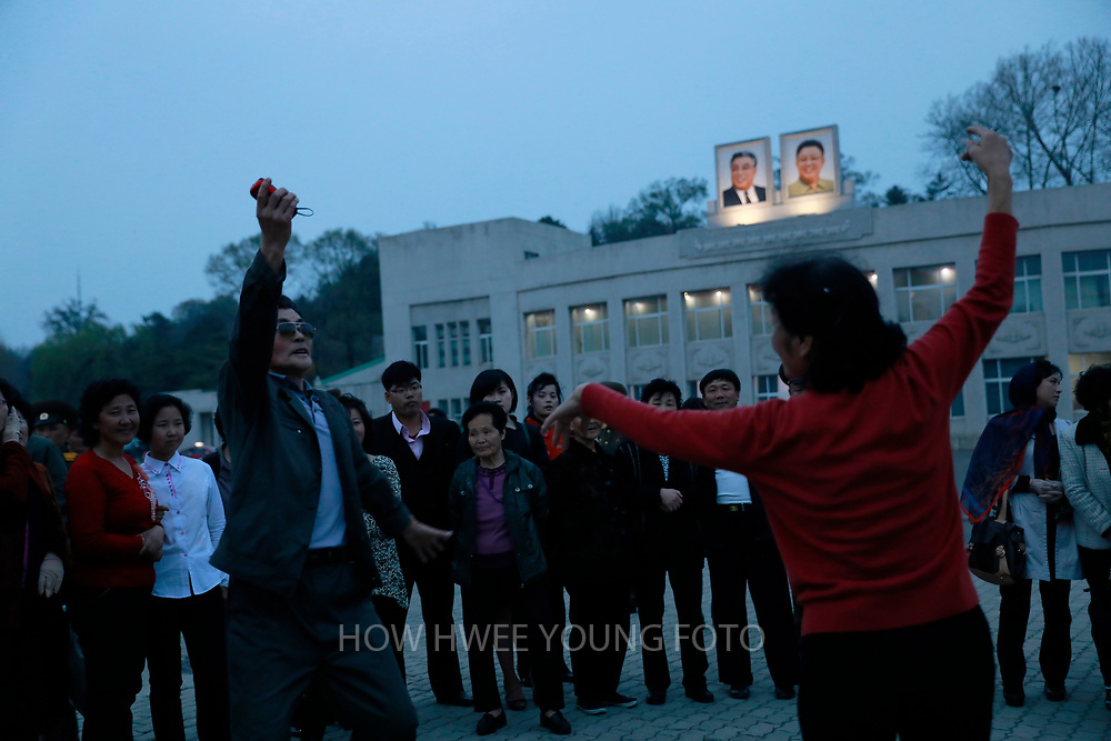 A picture made available on 17 April 2017 of North Koreans dancing in a park in Pyongyang, North Korea, 16 April 2017. A North Korean missile exploded within seconds of its launch on the east coast on 16 April, South Korean and US officials say as tensions rise in the region over nuclear issues.