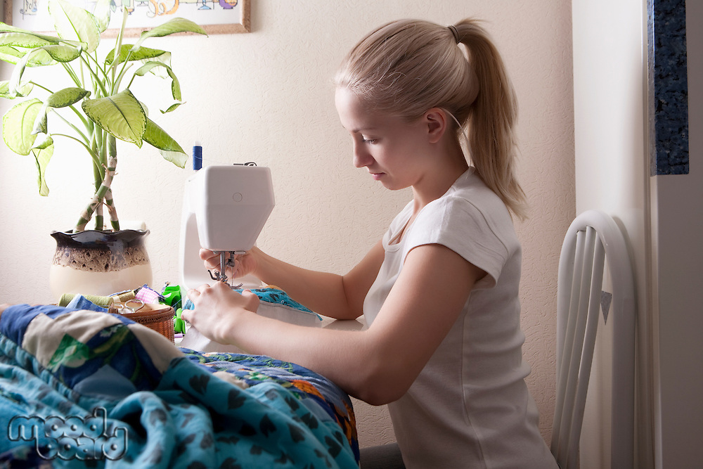 Young woman sits making patchwork at sewing machine