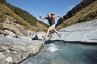 Hiker jumping across river