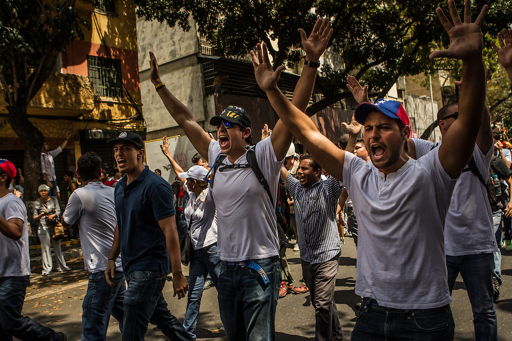 CARACAS, VENEZUELA - FEBRUARY 18, 2014:  Lopez supporters chant anti-government slogans as they walk infront of the armored vehicle carrying Leopoldo Lopez after he surrendered to the police. The government has said López is responsible for inciting recent street protests, that have killed three people. CREDIT: Meridith Kohut for The New York Times