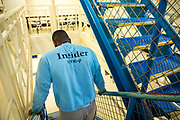 A prisoner wearing an insider jumper walking down the stairs on Benbow wing inside HMP/YOI Portland, a resettlement prison with a capacity for 530 prisoners. Dorset, United Kingdom.