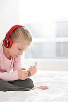 Cute girl listening music on smart phone in bedroom