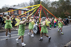 Windlesham, UK. 26 December, 2019. Competitors entertain spectators by dancing around a Maypole as they take part in the annual fancy dress Windlesham Boxing Day Pram Race charity event along a 3.5-mile course through Windlesham village with stops at local pubs along the route.