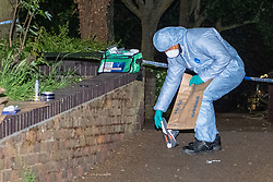 © Licensed to London News Pictures. 14/05/2020. London, UK. A forensic investigator holding an evidence bag picks up a shoe inside a cordon where police located two injured man. Police were called at around 1800BST on Wednesday, 13 May, to reports of a man with a knife in Lombard Road, SW11. There were also reports of a car in collision with a wall in Lombard Road. Officers attended the location and found two men injured - one had cuts to his arms and the other cuts to his legs. Officers believed the two men had been travelling in the car. Both have been taken to hospital, where their injuries are not believed to be life-threatening. Investigations at the scene led officers to Vicarage Crescent, SW11, where they found two other injured men. Both were taken to hospital with non life-threatening injuries. Photo credit: Peter Manning/LNP