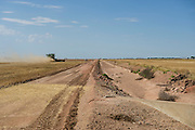 John Barrett drives a combine to harvest wheat along a small dirt road north of Martha, Oklahoma.